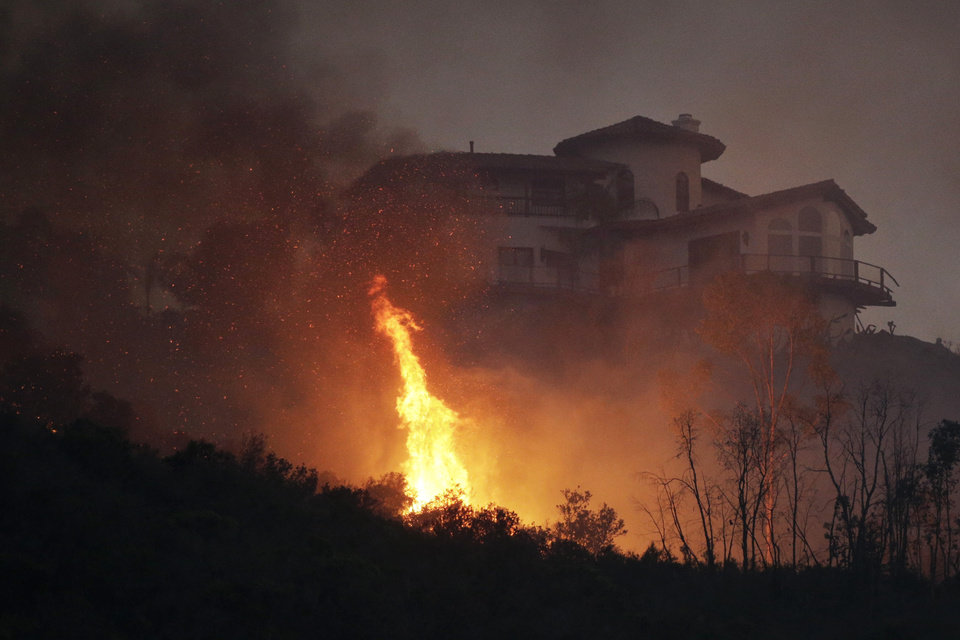 Photo - A wildfire burns near a home on Wednesday, May 14, 2014, in San Marcos, Calif. Flames engulfed suburban homes and shot up along canyon ridges in one of the worst of several blazes that broke out Wednesday in Southern California during a second day of a sweltering heat wave, taxing fire crews who fear the scattered fires mark only the beginning of a long wildfire season. (AP Photo)