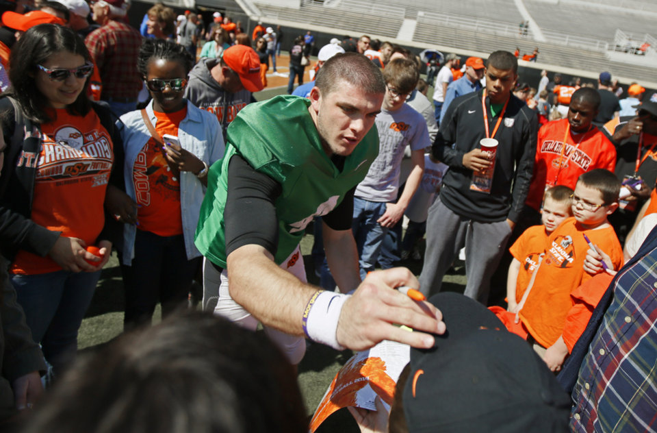 Photo - OSU's J.W. Walsh places a hat back on a young fan while signing autographs for fans after Oklahoma State's Orange Blitz football practice at Boone Pickens Stadium in Stillwater, Okla., Saturday, April 5, 2014.