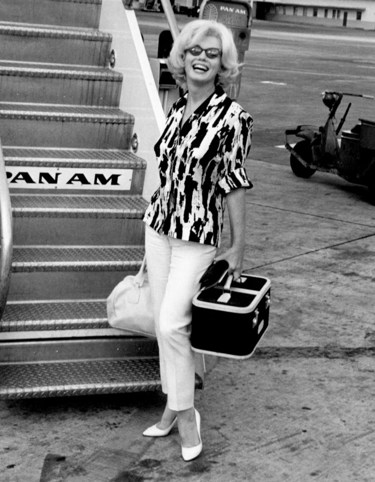 "From ""Marilyn in Fashion,"" by Christopher Nickens and George Zeno, Marilyn Monroe poses in a Jax outfit before boarding a plane in early 1962. The silk blouse in a bold black and white print has long sleeves, which Marilyn rolled up. She wore the ankle-length pants with her favorite Ferragamo pumps. Photo from author Zeno's personal collection. <strong></strong>"