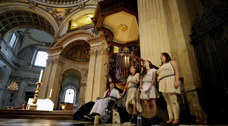 Photo -   Four women activists of the Occupy movement protest chained to the pulpit inside St Paul's Cathedral as preparations for evensong take place in London, Sunday, Oct. 14, 2012. Several supporters of the anti-corporate Occupy movement chained themselves to the pulpit of St. Paul's Cathedral during a service on Sunday in an action marking the anniversary of its now-dismantled protest camp outside the London landmark. (AP Photo/Alastair Grant)