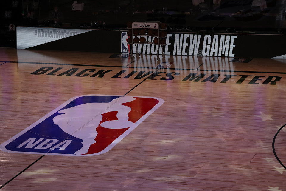 Photo - July 30, 2020; Lake Buena Vista, USA;  A general view the court with Black Lives Matter written above the NBA logo is seen at center court prior to the game between the LA Clippers and the Los Angeles Lakers at The Arena at ESPN Wide World Of Sports Complex. Mandatory Credit: Mike Ehrmann/Pool Photo via USA TODAY Sports
