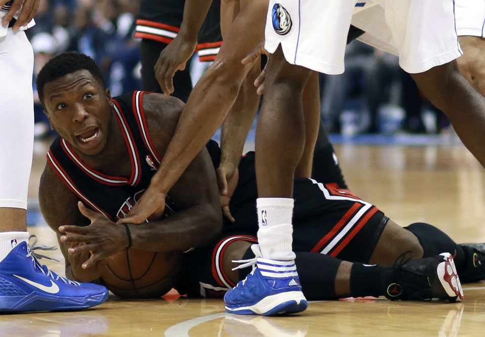 Chicago Bulls guard Nate Robinson (2) yells for a timeout after getting pinned on the floor defensively by Dallas Mavericks forward Shawn Marion, left, and Mavericks' Darren Collison, right, during the first half of an NBA basketball game, Saturday, March 30, 2013 in Dallas. (AP Photo/ Michael Mulvey)