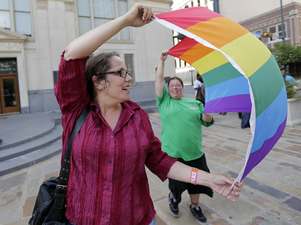Photo - Julie Pousson, left, and Jennifer Echeverry, right, celebrate after a non-discrimination ordinance was passed by the San Antonio city council, Thursday, Sept. 5, 2013, in San Antonio. The ordinance in part will prohibit discrimination based on sexual orientation and gender identity. (AP Photo/Eric Gay)