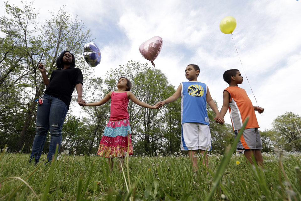 Photo - Residents listen to speeches before  releasing balloons in support of the three women found in a house on Seymour Avenue in Cleveland, Ohio, Thursday, May 9, 2013. Prosecutors said Thursday they may seek the death penalty against Ariel Castro, the man accused of imprisoning three women at his home for a decade, as police charged that he impregnated one of his captives at least five times and made her miscarry by starving her and punching her in the belly. (AP Photo/David Duprey)