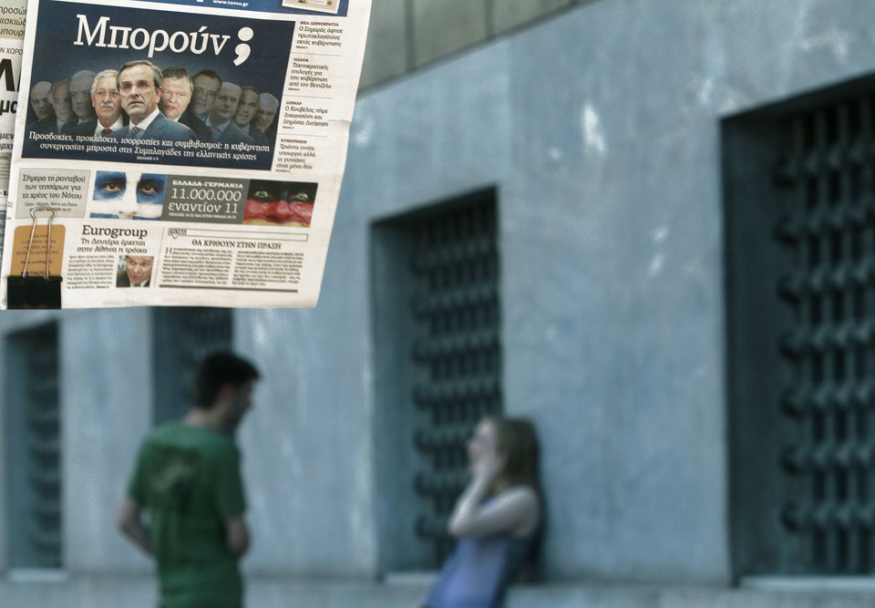 A man and woman stand next to a kiosk that sells newspapers as the newspaper on the left shows the new Greek government with title in Greeks
