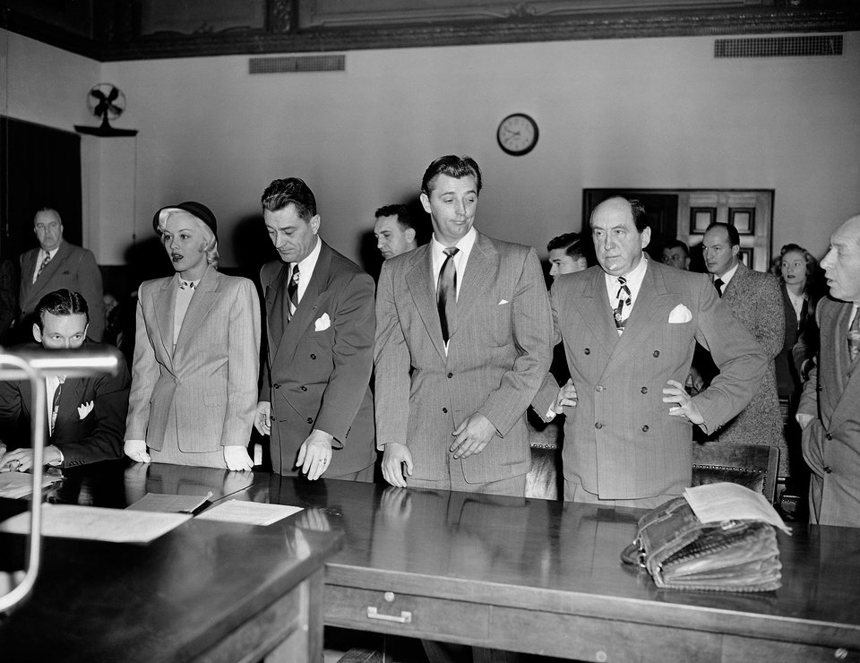 "FILE - In this Feb. 9, 1949 file photo, actor Robert Mitchum, center right, and actress Lila Leeds, left, are sentenced to 60 days in jail on charges of conspiracy to possess marijuana cigarettes in Los Angeles. On the occasion of  ""Legalization Day,"" Thursday, Dec. 6, 2012, when Washington's new law takes effect, AP takes a look back at the cultural and legal status of the ""evil weed"" in American history. (AP Photo, File)"