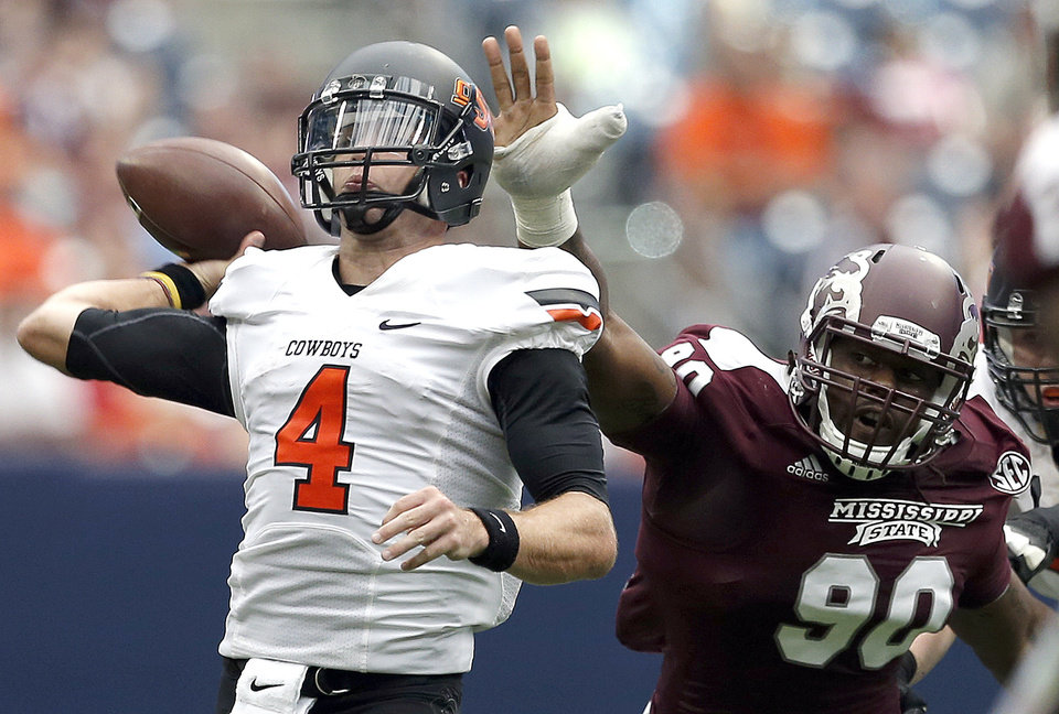 Photo - Oklahoma State's J.W. Walsh (4) throws a pass as he is pressured by Mississippi State's Denico Autry (90) during second half of the AdvoCare Texas Kickoff college football game between the Oklahoma State University Cowboys (OSU) and the Mississippi State University Bulldogs (MSU) at Reliant Stadium in Houston, Saturday, Aug. 31, 2013. Photo by Sarah Phipps, The Oklahoman
