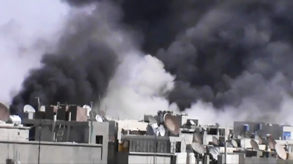 Photo -   In this image made from amateur video released by the Shaam News Network and accessed Wednesday, April 18, 2012, smoke rises from buildings following purported shelling in Khaldiyeh district, Homs, Syria. Nearly a week after a cease-fire took effect, Syrian troops pounded a rebel stronghold Wednesday as the country's foreign minister met with his Chinese counterpart in Beijing during the latest round of talks aimed at preventing the truce from unraveling.(AP Photo/Shaam News Network via AP video) TV OUT, THE ASSOCIATED PRESS CANNOT INDEPENDENTLY VERIFY THE CONTENT, DATE, LOCATION OR AUTHENTICITY OF THIS MATERIAL