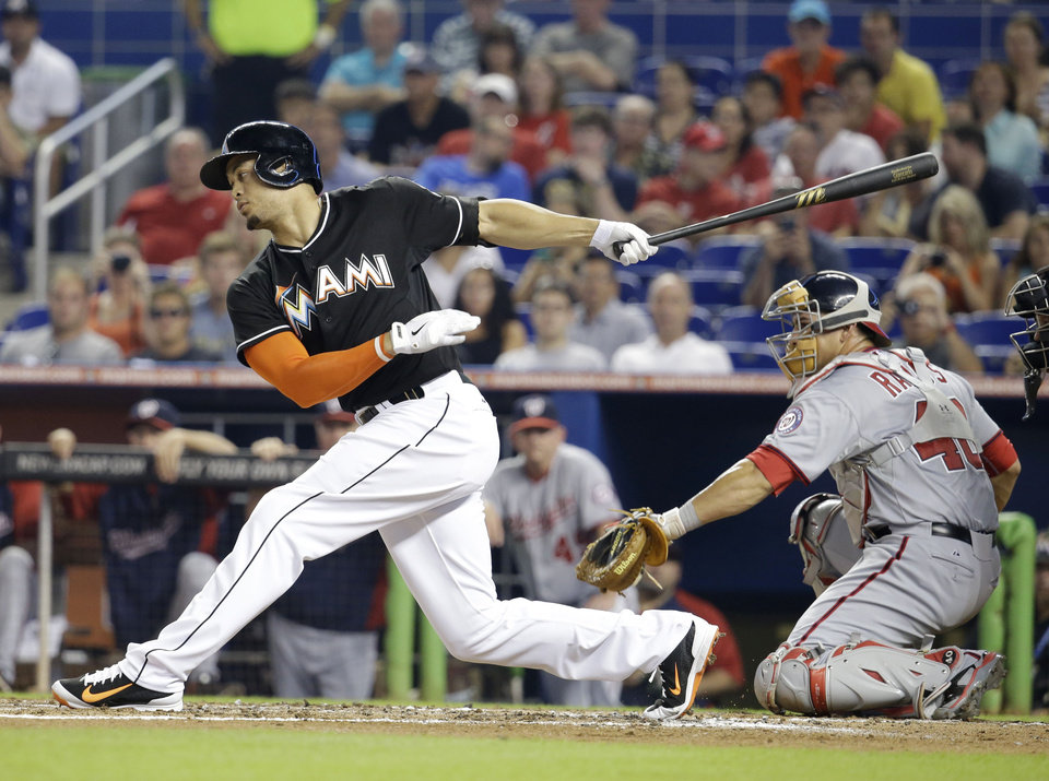 Photo - Miami Marlins' Giancarlo Stanton, left, strikes out to send the first inning as Washington Nationals catcher Wilson Ramos (40) looks on during a baseball game, Monday, July 28, 2014, in Miami. (AP Photo/Lynne Sladky)