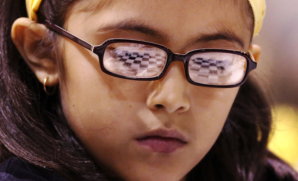 The chess board is seen as a reflection in the glasses of Camila Santa Maria, a third-grader at Parkview Elementary.