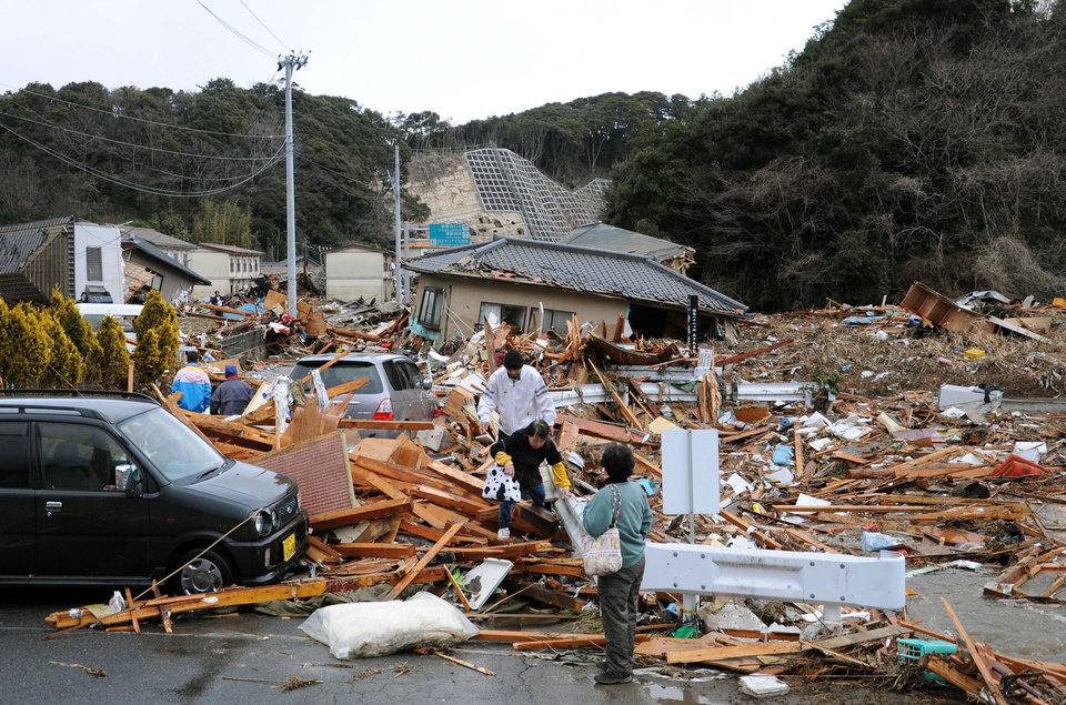 Photo - Residents walk through the rubles of residents collapsed by a powerful earthquake in Iwaki, Fukushima prefecture (state), Japan, Friday, March 11, 2011. The largest earthquake in Japan's recorded history slammed the eastern coast Friday. (AP Photo/Kyodo News) JAPAN OUT, MANDATORY CREDIT, FOR COMMERCIAL USE ONLY IN NORTH AMERICA ORG XMIT: TTX802