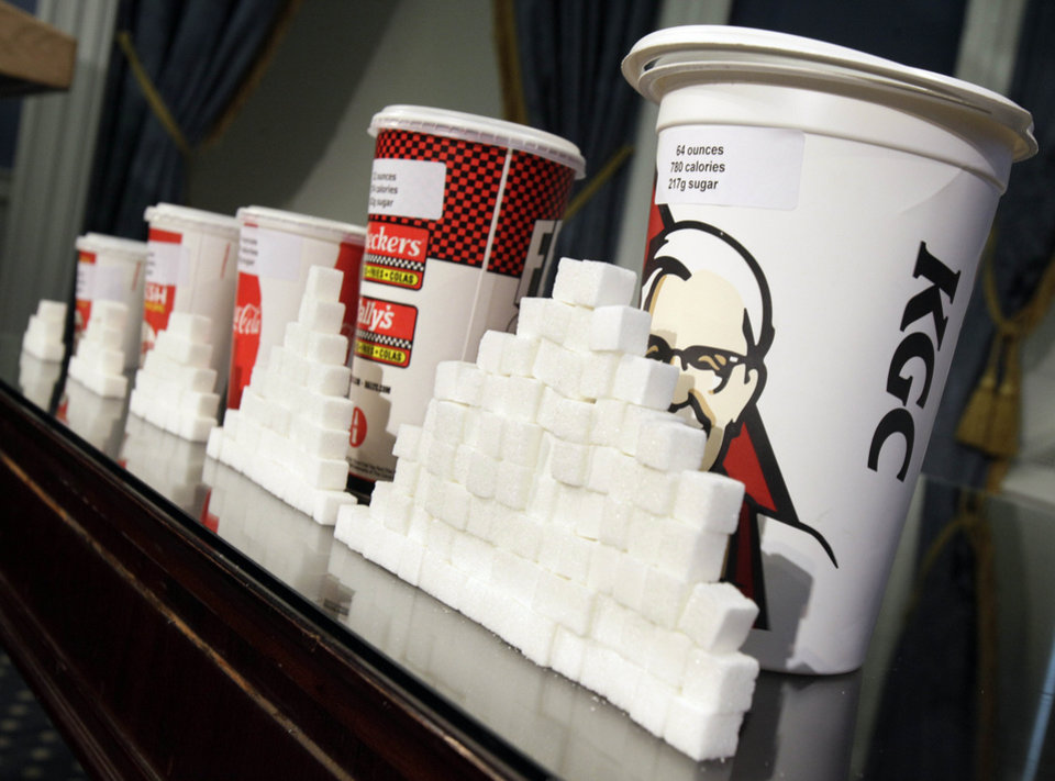 Photo - FILE - This May 31, 2012 file photo shows a display of various size cups and sugar cubes at a news conference at New York's City Hall. A judge struck down New York City's groundbreaking limit on the size of sugar-laden drinks Monday, March 11, 2013 shortly before it was set to take effect, agreeing with the beverage industry and other opponents that the rule is arbitrary in applying to only some sweet beverages and some places that sell them. (AP Photo/Richard Drew, File)