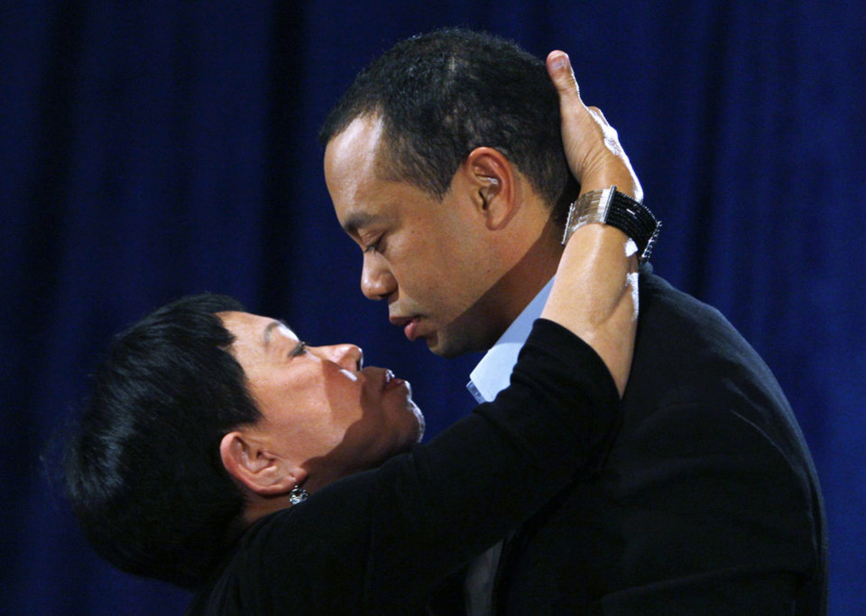 Photo - Tiger Woods hugs his mother Kultida Woods after making a statement at the Sawgrass Players Club, Friday, Feb. 19, 2010, in Ponte Vedra Beach, Fla. (AP Photo/Joe Skipper, Pool) ORG XMIT: TWP103