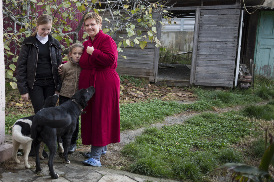 Photo - In this photo taken on Wednesday, Nov. 27, 2013, Alexandra Krivchenko, right, and her children, center, play with the dogs in the yard of a house sandwiched between the railway and a federal highway (seen in the background) in the village of Vesyoloye outside Sochi, Russia. As the Winter Games are getting closer, many Sochi residents are complaining that their living conditions only got worse and that authorities are deaf to their grievances. (AP Photo/Alexander Zemlianichenko)