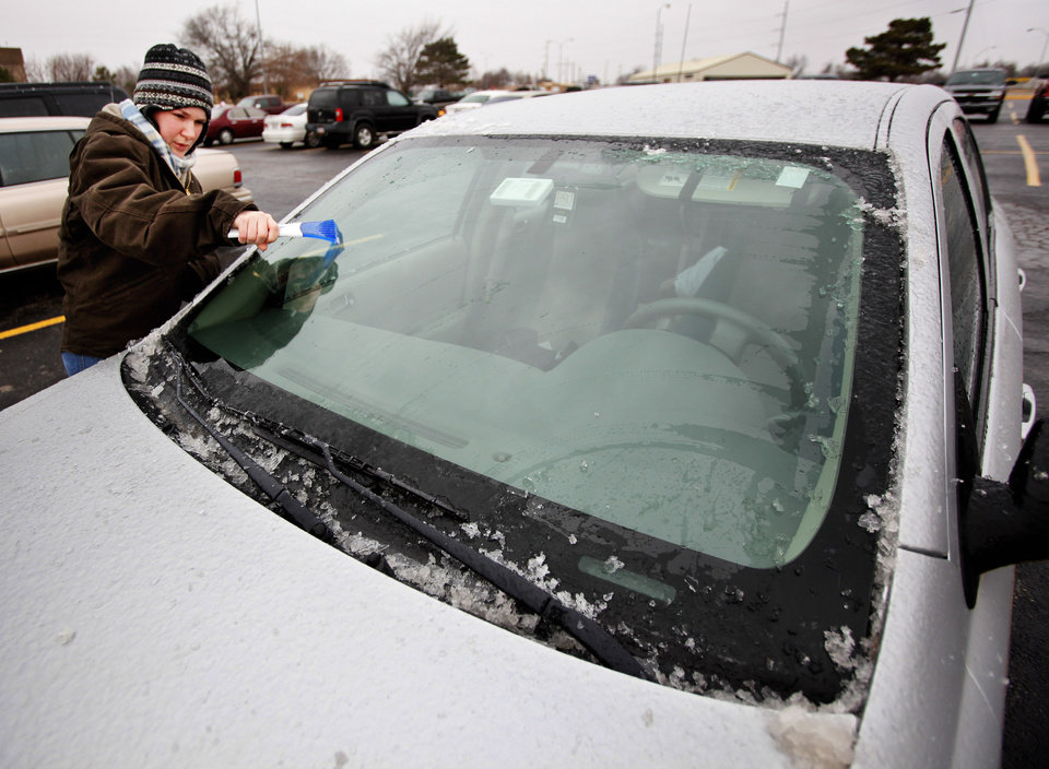 Photo - Amanda Knotts, nursing student from Yukon, removing ice from her windshield after classes were cancelled on the OSU OKC campus due to a winter storm moving through the metro in Oklahoma City Thursday, Jan. 28, 2010. Photo by Paul B. Southerland, The Oklahoman