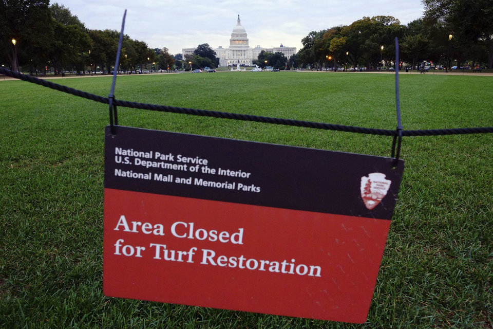 Photo - The U.S. Capital is seen behind an area closed for restoration sign on the National Mall in Washington, Tuesday, Oct. 1, 2013. The National Parks Service will begin to close many of the nation's national parks after Congress locked in a battle over the Affordable Health Care Act failed to pass a budget resulting in the shuttering of many of the government's operations. (AP Photo/J. David Ake)