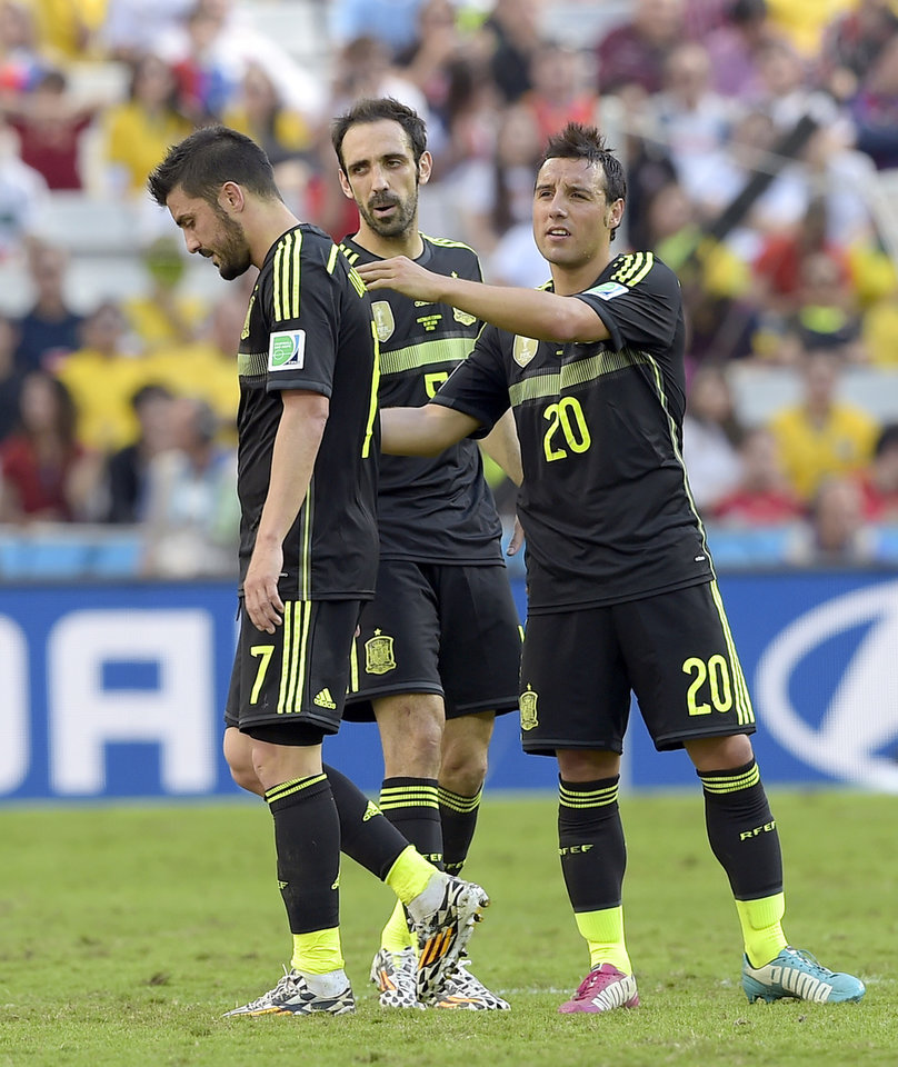 Photo - Spain's Santi Cazorla comforts Spain's David Villa as he leaves the pitch during the group B World Cup soccer match between Australia and Spain at the Arena da Baixada in Curitiba, Brazil, Monday, June 23, 2014. Center is Spain's Juanfran.(AP Photo/Manu Fernandez)