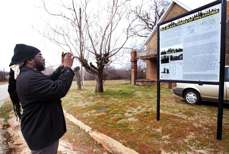 Photo - The Oklahoma Historical Society's All-Black Towns Project includes placing markers in 13 surviving towns, including this one in Boley, where Langston University Marching Pride Band Director Larry Birden takes a photo of the sign in this file photo. PHOTO BY CORY YOUNG, TULSA WORLD