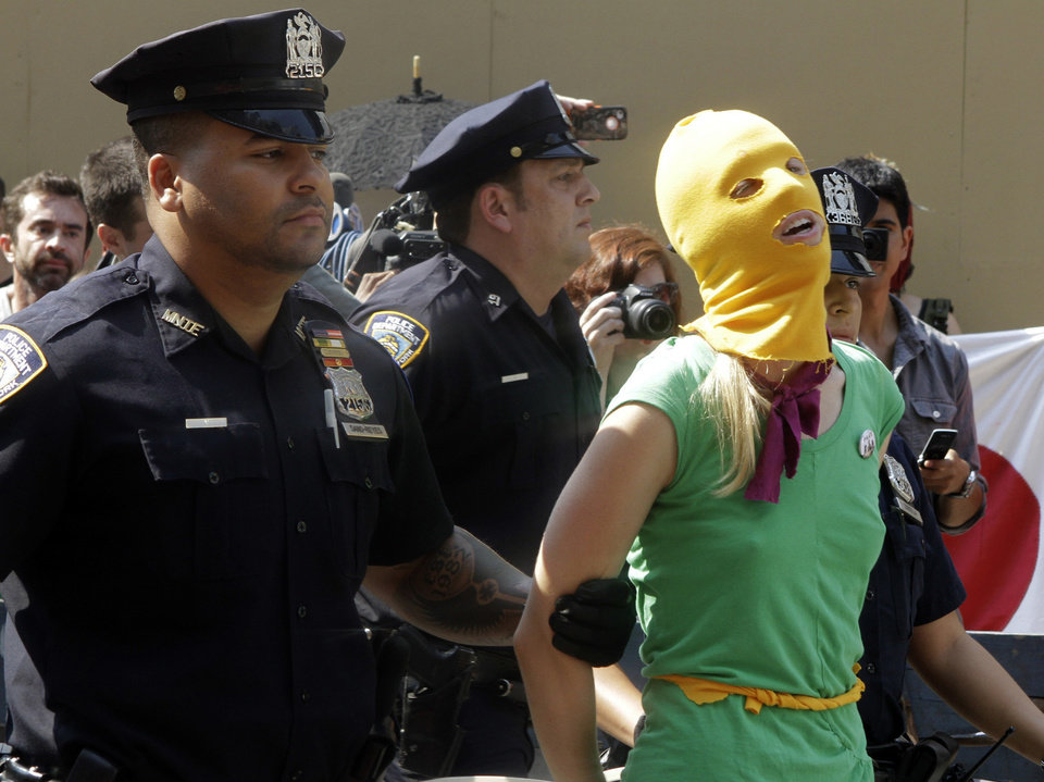 Photo -   A protester is arrested during a demonstration in front of the Russian consulate in support of Russian punk band Pussy Riot, Friday, Aug. 17, 2012 in New York. A Russian judge found three members of the provocative punk band guilty of hooliganism on Friday, in one of the most closely watched cases in recent Russian history. The three were arrested in March after a guerrilla performance in Moscow's main cathedral calling for the Virgin Mary to protect Russia against Vladimir Putin, who was elected to a new term as Russia's president a few days later. (AP Photo/Alex Katz)
