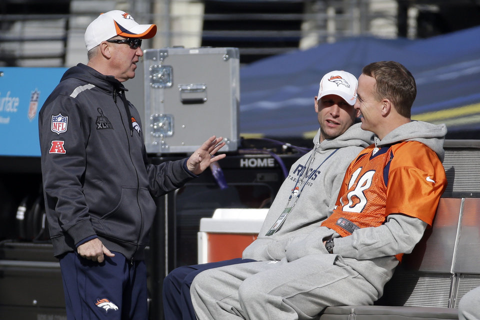 Photo - Denver Broncos head coach John Fox, left, talks with quarterback Peyton Manning (18) in MetLife Stadium on Saturday, Feb. 1, 2014, in East Rutherford, N.J. The Broncos are scheduled to play the Seattle Seahawks in the NFL Super Bowl XLVIII football game Sunday. (AP Photo/Mark Humphrey)