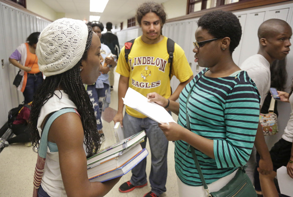 Photo - In This Aug. 29, 2014, photo Erin Nwachukwu right, goes over class schedules with her friends, Khalidah Ahmad, left, and Yosef Smith, center, during orientation day at Lindblom Math and Science Academy in Chicago. A new study has found that, while Americans are mistrustful of each other and institutions -- from government to corporations and the media -- young people are among the least likely age group to have confidence in those institutions, especially since the terror attacks of Sept. 11, 2001. Nwachukwu, 16, says it's been difficult for her generation to keep the faith through multiple political scandals, a recession and various shootings — including the recent shooting of a young man in Ferguson, Missouri.