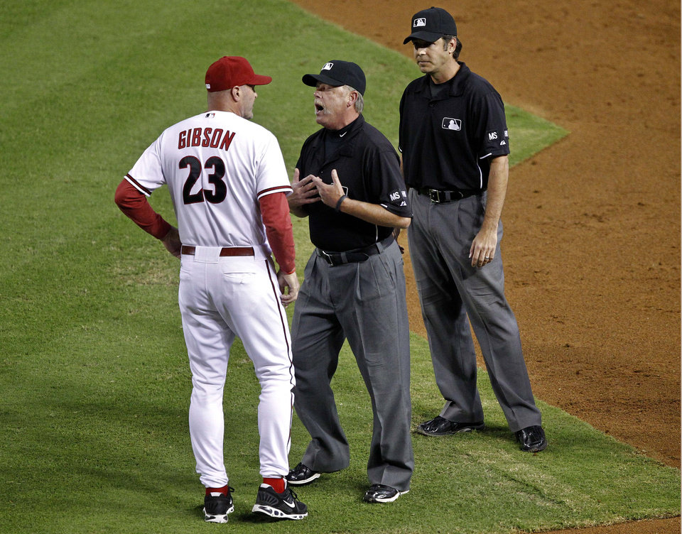 Photo -   Arizona Diamondbacks manager Kirk Gibson (23) argues with crew chief Jim Reynolds, center, after James Hoye, right, ruled Diamondbacks' Paul Goldschmidt was safe at first with a base hit and was then overturned by the umpires during the fifth inning of a baseball game against the San Francisco Giants, Friday, Sept. 14, 2012,in Phoenix. (AP Photo/Matt York)