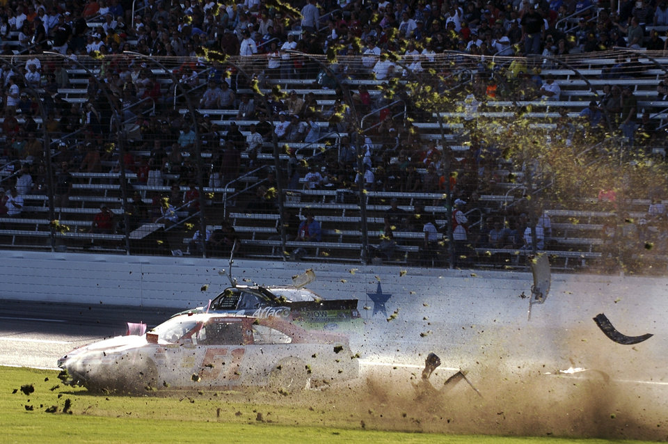 Photo -   Debris flies as AJ Allmendinger (51) slides through the infield after colliding with Carl Edwards, rear, during the NASCAR Sprint Cup Series auto race at Texas Motor Speedway, Sunday, Nov. 4, 2012, in Fort Worth, Texas. (AP Photo/Randy Holt )