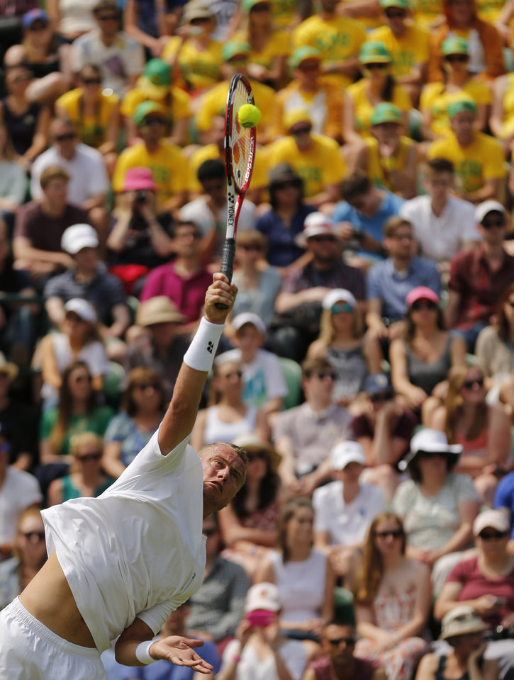 Photo - Lleyton Hewitt of Australia serves  to Michal Przysiezny of Poland during their first round match at the All England Lawn Tennis Championships in Wimbledon, London, Tuesday, June 24, 2014. (AP Photo/Ben Curtis)