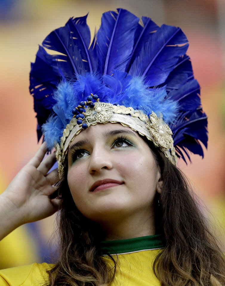 Photo - A spectator adjusts her headdress before the start of the group A World Cup soccer match between Cameroon and Croatia at the Arena da Amazonia in Manaus, Brazil, Wednesday, June 18, 2014. (AP Photo/Themba Hadebe)