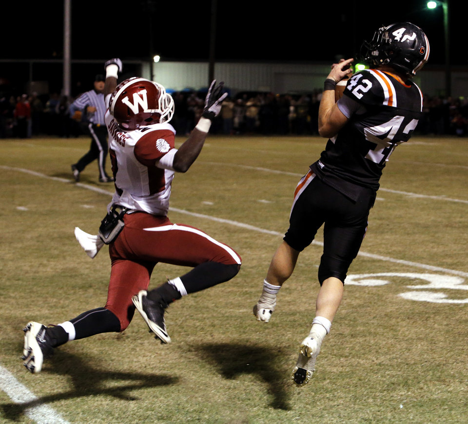 Wayne's Ryan Welch (42) catches a pass on his way to the end zone for a first-half touchdown as Wynnewood's Pete Carter (2) defends in high school Football on Friday, Oct. 26, 2012 in Wayne, Okla.  Photo by Steve Sisney, The Oklahoman