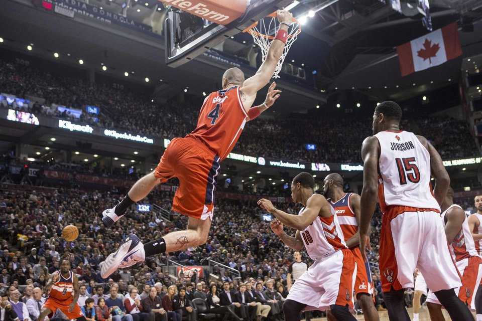 Photo - Washington Wizards' Marcin Gortat, center, swings from the hoop as his missed shot rebounds out to Wizards' Martell Webster, left, during first half NBA basketball action against Toronto Raptors in Toronto, Thursday, Feb. 27, 2014. (AP Photo/The Canadian Press, Chris Young)