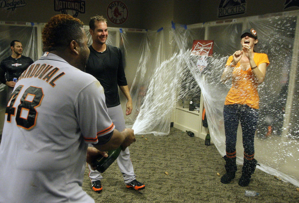 Photo -   San Francisco Giants' Pablo Sandoval (48) sprays Nicole Vogelsong, wife of Giants pitcher Ryan Vogelsong, in the locker room after the Giants defeated the Cincinnati Reds 6-4 in Game 5 of the National League division baseball series, Thursday, Oct. 11, 2012, in Cincinnati. The Giants won the final three games, all in Cincinnati, and advanced to the NL championship series. (AP Photo/David Kohl)