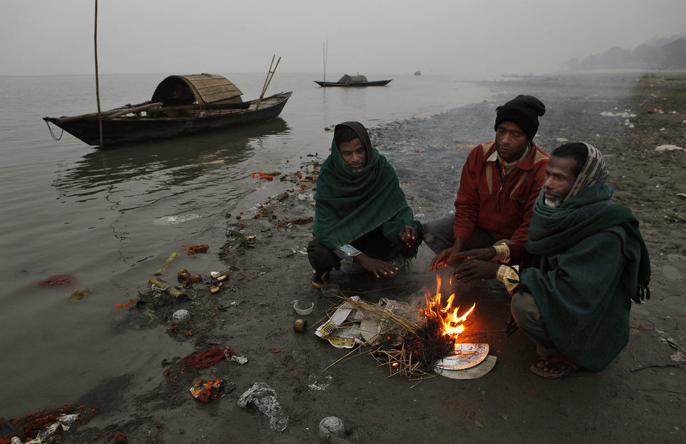 Indian people warm themselves near a fire on a cold and foggy evening near the river Brahmaputra in Gauhati, India, Tuesday, Jan. 8, 2013. North India continues to face below average weather conditions with dense fog affecting flights and trains. (AP Photo/Anupam Nath)