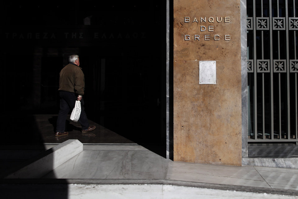 Photo - A man enters the headquarters of Bank of Greece, in central Athens, on Monday, Dec. 10, 2012. In an attempt to generate stronger participation in its key government bond buyback program, Greece on Monday extended the deadline for banks, funds and investors who own its debt to declare whether they will sell their holdings back at a heavy discount. (AP Photo/Petros Giannakouris)