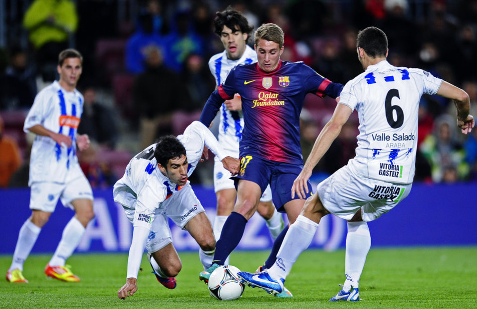 FC Barcelona's Deulofeu, second right, duels for the ball against Alaves's Agustin, right, during a Copa del Rey soccer match at the Camp Nou stadium in Barcelona, Spain, Wednesday, Nov 28, 2012. (AP Photo/Manu Fernandez)