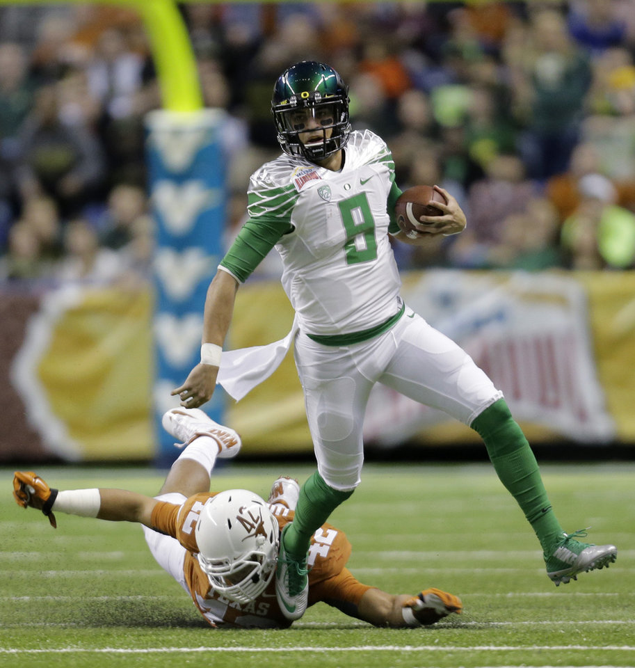 Photo - FILE - In this Dec. 30, 2013, file photo, Oregon's Marcus Mariota (8) is pursued by Texas' Caleb Bluiett (42) during the first quarter in the Valero Alamo Bowl NCAA college football game in San Antonio. If he stays healthy, Mariota is one of the nation's best dual-threat quarterbacks and could find himself holding that bronze trophy. (AP Photo/Eric Gay, File)