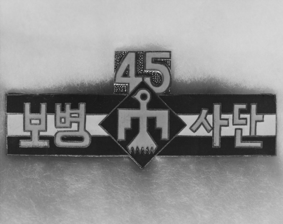 Photo - Katusa's of the 45th Division now have a distinctive service badge of their own, designed and prepared by the Thunderbirds for presentation to Korean troops who served with the division during combat.  Maj. Gen P.D. Ginder, 45th Division commander, fostered the idea, hoping to make the Korean troops, detached from their own army, feel themselves a more integral part of the division.  He wanted to express, in the form of an award, the division's appreciation for their efforts while serving with the Thunderbirds.  What originally started out to be a regimental crest ended in the present form of a service badge, moulding the best ideas of the artists and draftsmen assigned the project.  Photographer and original date unknown.  Entered the library 02/11/1954.