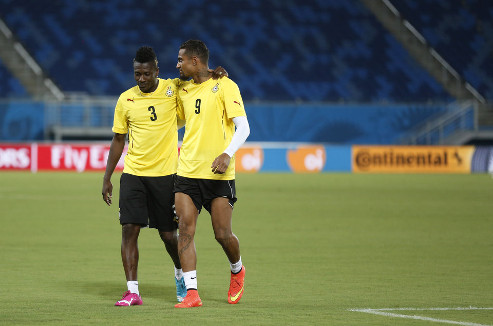 Photo - Ghana's Asamoah Gyan, left, and Kevin-Prince Boateng converse during an official training session the day before the group G World Cup soccer match between Ghana and the United States at the Arena das Dunas in Natal, Brazil, Sunday, June 15, 2014.  (AP Photo/Dolores Ochoa)