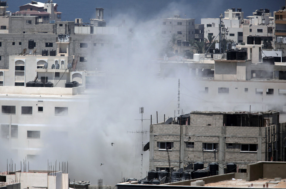 Photo - Smoke rises from a building that was hit with an Israeli strike in Gaza City, Tuesday, July 29, 2014. Israel struck symbols of Hamas' control of Gaza and the strip's only power plant on Tuesday, escalating its military campaign against the Islamic militant group with the heaviest bombardment in the fighting so far.(AP Photo/Khalil Hamra)