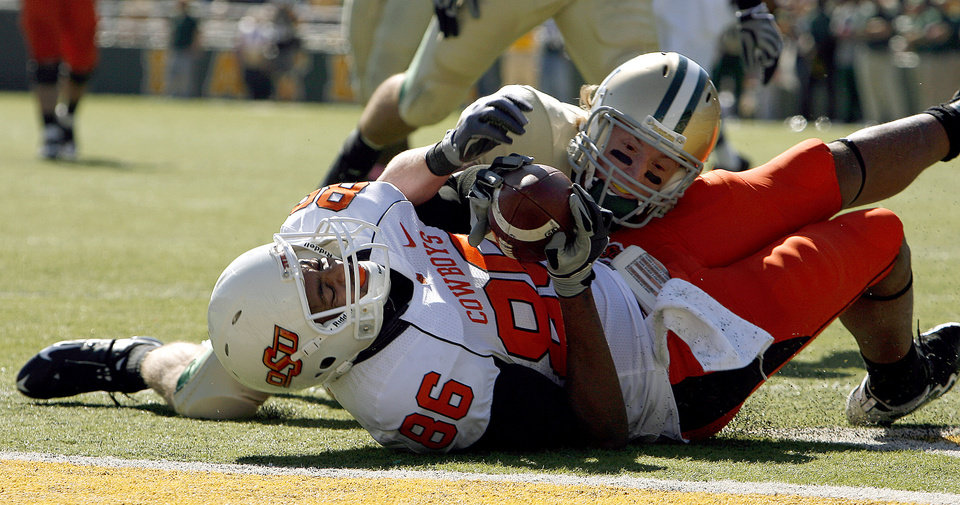 Photo - OSU's Wilson Youman (86) scores a touchdown as Baylor's Jordan Salubi (21) tackles him during the college football game between Baylor University and Oklahoma State University (OSU) at Floyd Casey Stadium in Waco, Texas, Saturday, Oct. 24, 2009.  Photo by Sarah Phipps, The Oklahoman