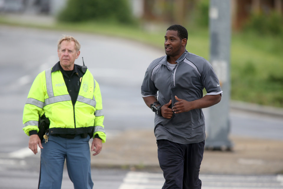 Photo - A Cobb County Police officer, left, escorts a FedEx employee as he crosses McCollum Parkway leaving the blocked off area after an early morning workplace shooting at the Airport Road FedEx facility Tuesday April 29, 2014, in Kennesaw, Ga. A shooter opened fire at a FedEx center wounding at least six people before police swarmed the facility. The shooter was found dead from an apparent self-inflicted gunshot wound. (AP Photo/Jason Getz)
