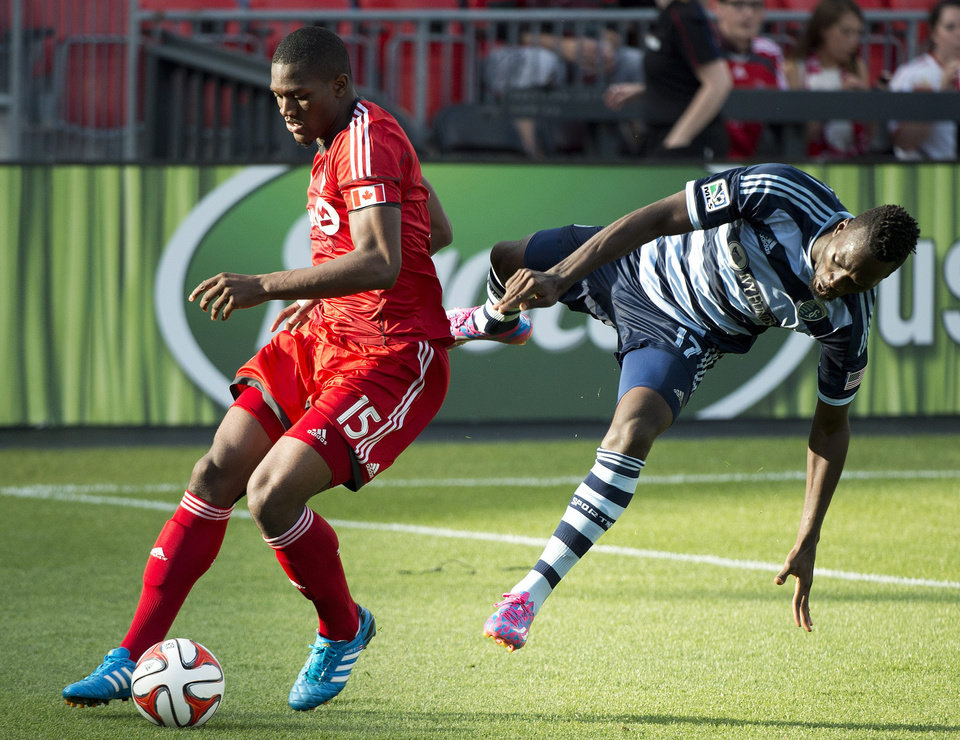 Photo - Toronto FC defender Doneil Henry, left, vies for the ball against Sporting Kansas City forward C.J. Sapong during the first half of an MLS soccer game Saturday, July 26, 2014, in Toronto. (AP Photo/The Canadian Press, Nathan Denette)