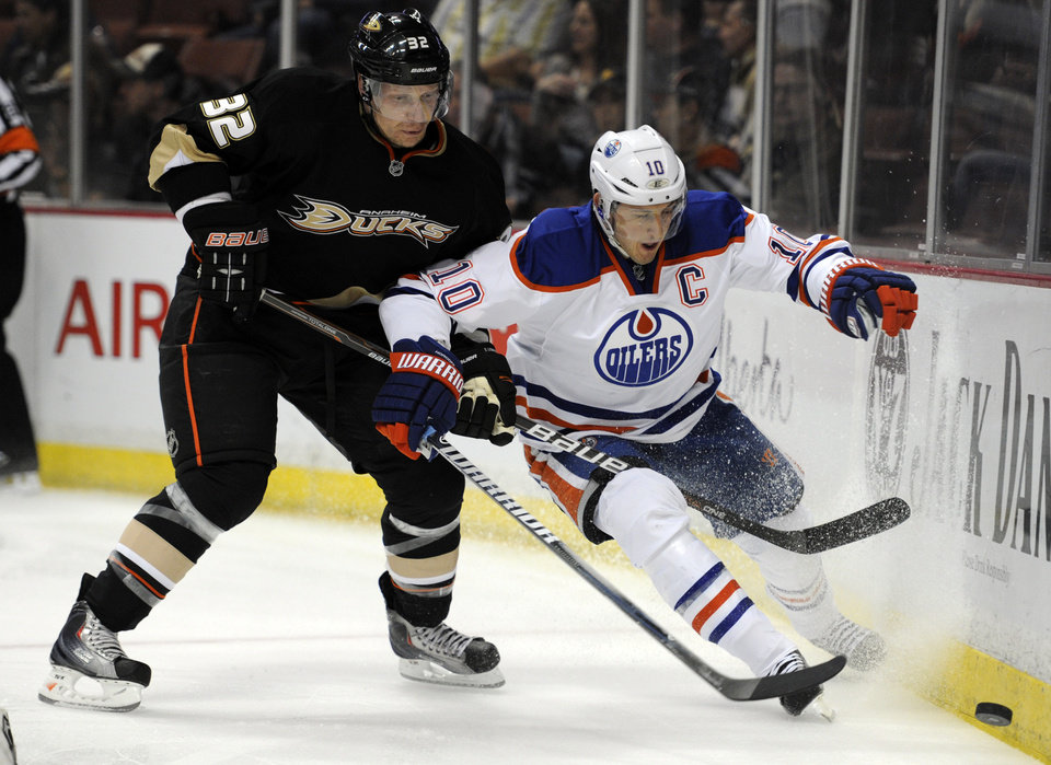 Anaheim Ducks defenseman Toni Lydman (32), of Finland, and Edmonton Oilers center Shawn Horcoff (10) battle for the puck in the period of an NHL hockey game in Anaheim, Calif., Monday, March 5, 2012. (AP Photo/Lori Shepler)