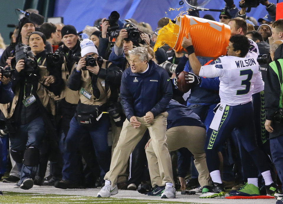 Photo - Seattle Seahawks quarterback Russell Wilson (3) dumps Gatorade on head coach Pete Carroll near the end of the NFL Super Bowl XLVIII football game against the Denver Broncos, Sunday, Feb. 2, 2014, in East Rutherford, N.J. Seattle won 43-8. (AP Photo/Matt York)
