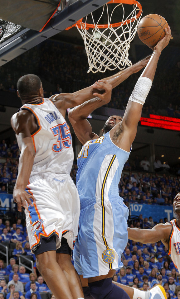 Photo - Denver's Nene (31) goes to the basket on Oklahoma City's Kevin Durant (35) during the first round NBA playoff game between the Oklahoma City Thunder and the Denver Nuggets on Sunday, April 17, 2011, in Oklahoma City, Okla. Photo by Chris Landsberger, The Oklahoman