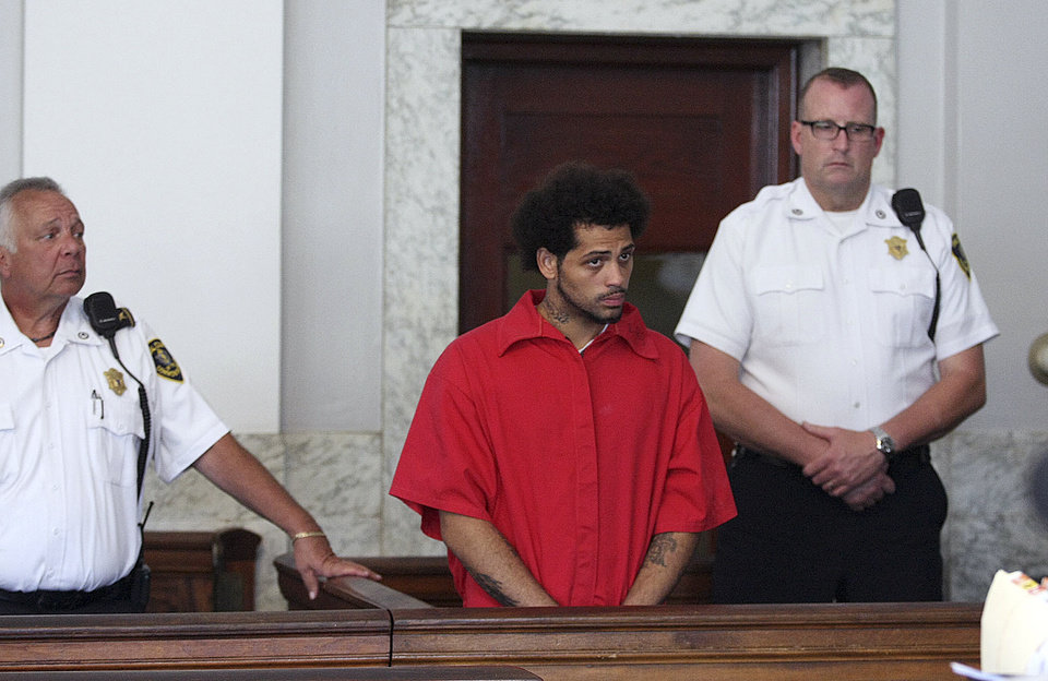 Photo - Carlos Ortiz, left, stands in Attleboro District Court for his arraignment on weapons charges, Friday, June 28, 2013 in Attleboro, Mass. Ortiz was arrested Wednesday in Bristol, Conn., in connection with the murder case against former New England Patriots tight end Aaron Hernandez , now charged in the murder of Odin Lloyd.   (AP Photo/The Boston Globe, George Rizer, Pool)