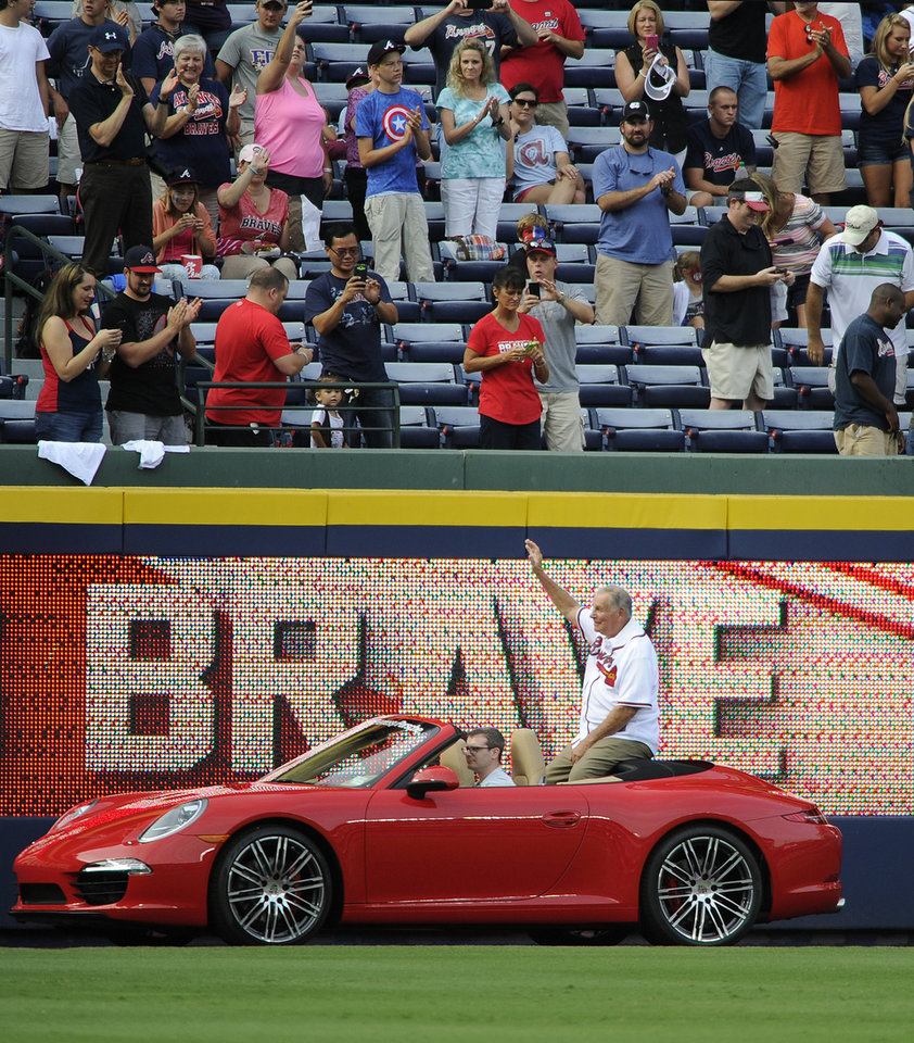 Photo - Former Atlanta Braves manager Bobby Cox waves to fans as he and fellow recent Baseball Hall of Fame inductees Greg Maddux and Tom Glavine were honored before a baseball game between the Braves and the Washington Nationals on Friday, Aug. 8, 2014, in Atlanta. (AP Photo/David Tulis)