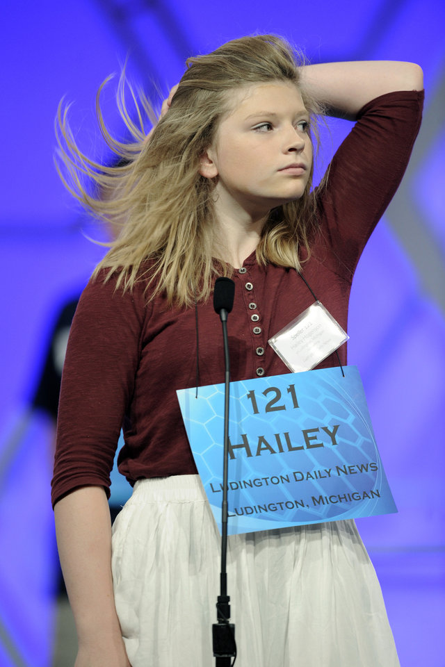 "Photo - Hailey Hogenson, 13, of Ludington, Mich., flips her hair before spelling the word ""amphibious""  during the 2015 Scripps National Spelling Bee in Oxon Hill, Md., Wednesday, May 27, 2015. (AP Photo/Cliff Owen)"