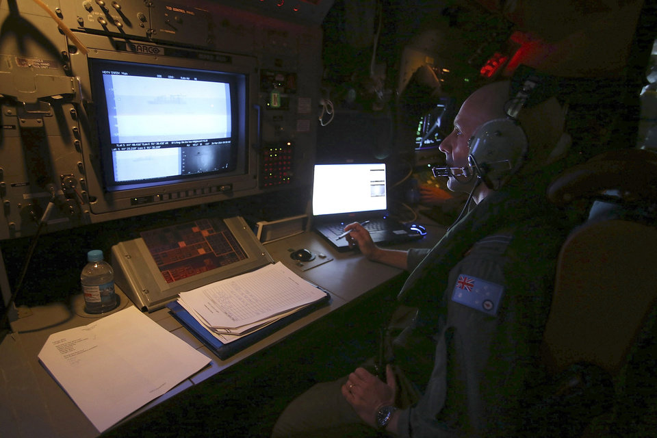 Photo - In this Wednesday, March 26, 2014 photo, Sensor Employment Manager Neville Dawson keeps watch on the radar on board a Royal Australian Air Force AP-3C Orion during a search for the missing Malaysia Airlines Flight 370 in the southern Indian Ocean. A French satellite scanning the Indian Ocean for remnants of the missing jetliner found a possible plane debris field containing 122 objects, a top Malaysian official said Wednesday, calling it