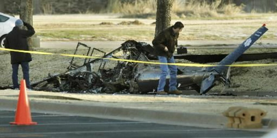 Photo - Investigators with the FAA look over the wreckage of a medical helicopter which crashed in front of the Saint Ann Retirement Center on Britton Road between Rockwell and Council Roads in Oklahoma City, OK, Friday, February 22, 2013. Two people were killed in the crash. By Paul Hellstern, The Oklahoman